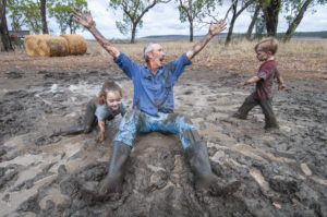 man rejoices in a puddle with two small children